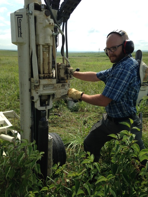 Graduate student Seton Bachle taking soil cores to count the root density of dogwood shrubs at Konza Prairie Biological Station.